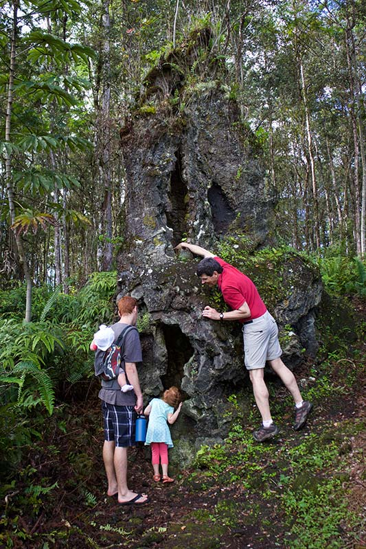 Little girl looking up though a lava tree mold as her grandfather shower his hand out of the top.