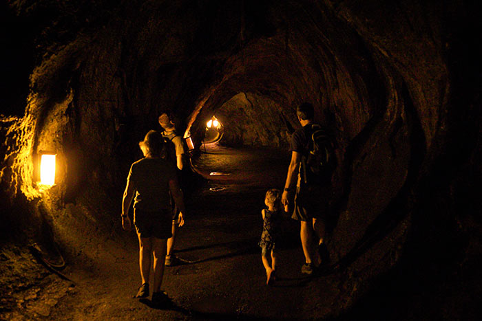 family walking through Thurston lava tube while. Lit up by lights