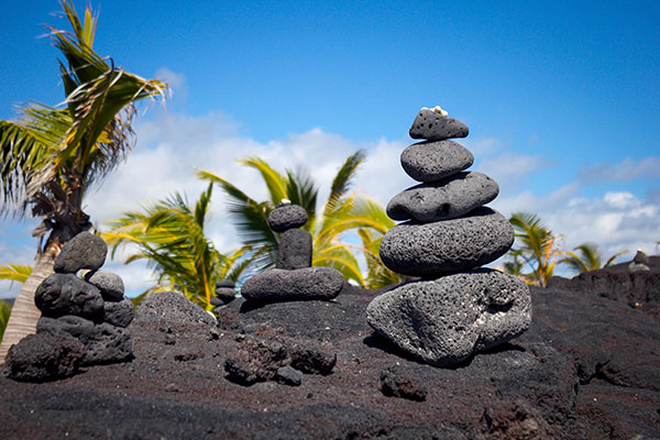 6 rocks piled on one another from largest to smallest with palm tress in the distance