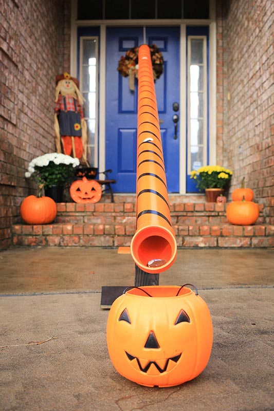 candy chute with halloween candy bucket underneath it.