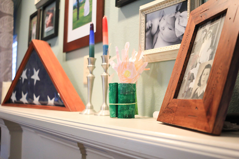 Fireplace mantel with American flag and family photos.