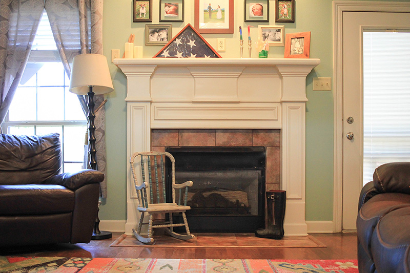Fireplace with child's rocking chair and family photos.