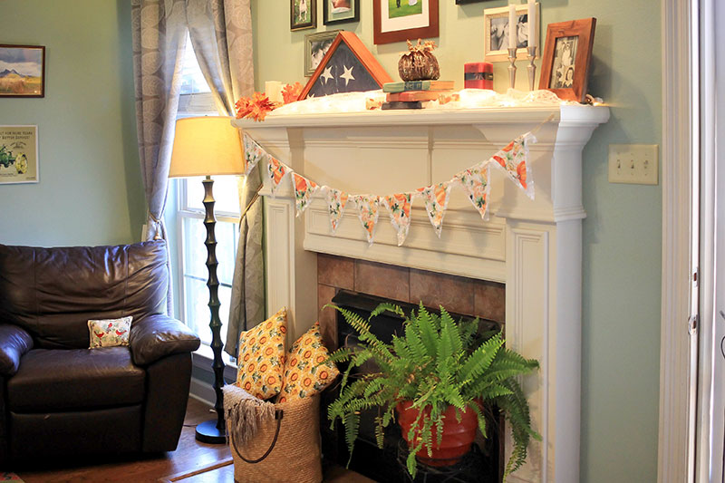 Fall fireplace with baskets, pillows, plants and fall pennant