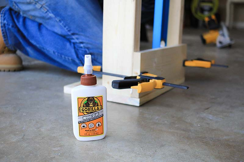 Gorilla glue in foreground with clamps holding the base of magazine rack in background.