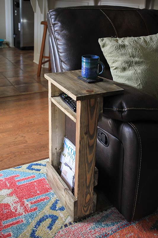 Completed slide under sofa table with coffee mug, remote and magazines.