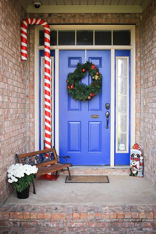 Striped PVC candy cane next to blue door.
