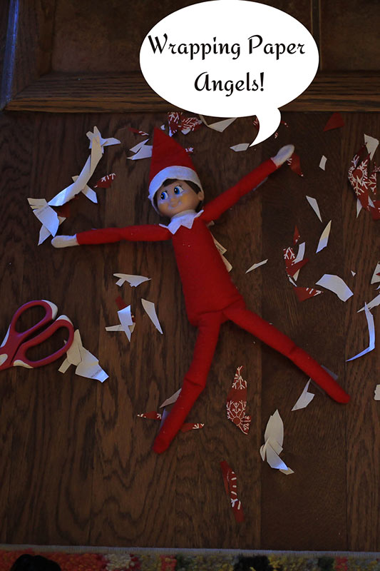 elf doing snow angels from cut up wrapping paper
