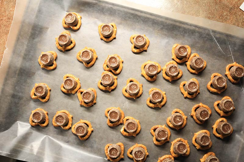 A bunch of pretzel and rolos on a cookie sheet