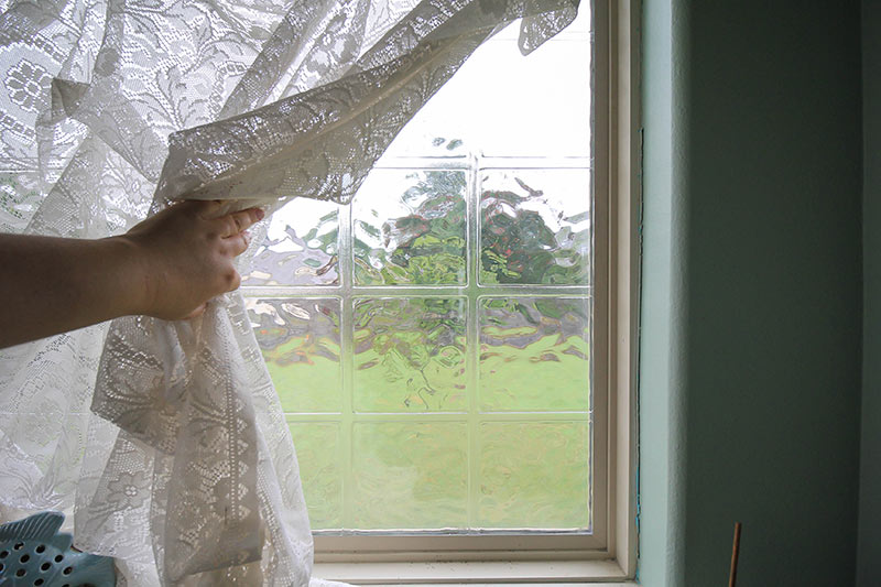 block glass behind a lace curtain