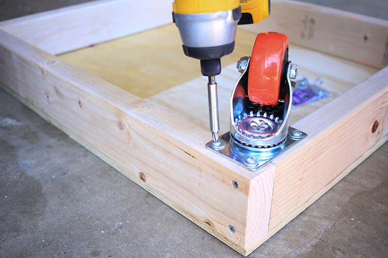 Attaching the caster wheel to the 2x4 bottom shelf