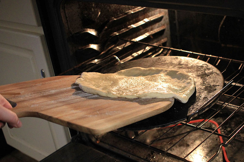 Putting pizza dough into oven