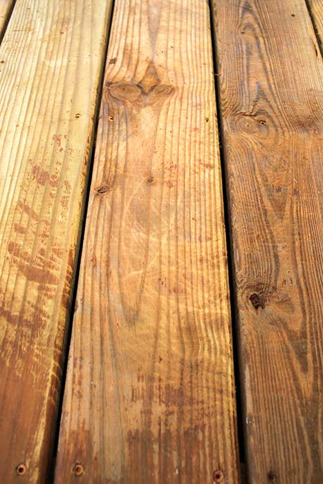 Scratch marks left on deck boards by using pressure washer surface cleaner.