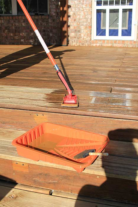 Using a paint pad applicator to apply deck stain and sealer.