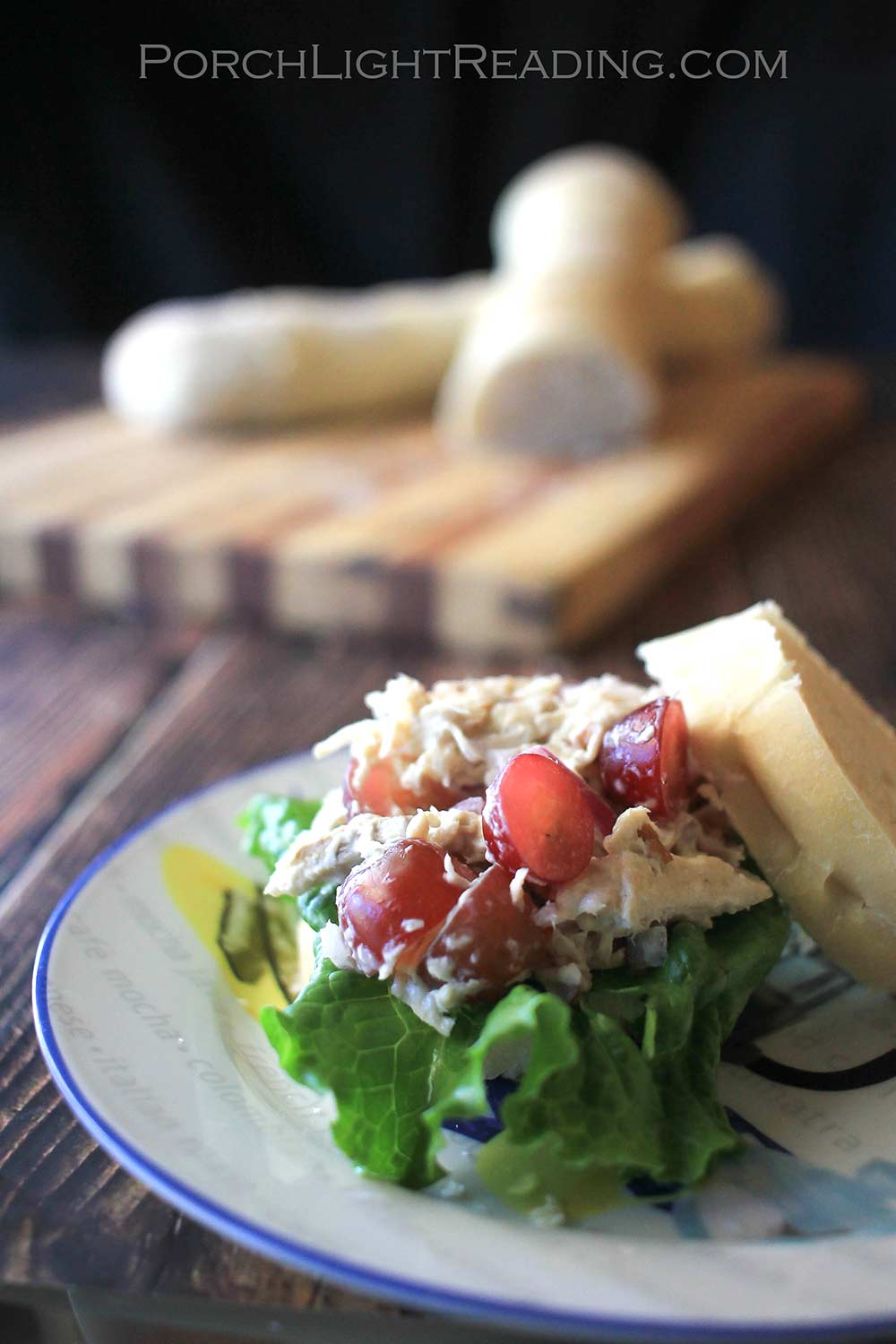 Chicken salad on a bed of lettuce with sliced grapes.