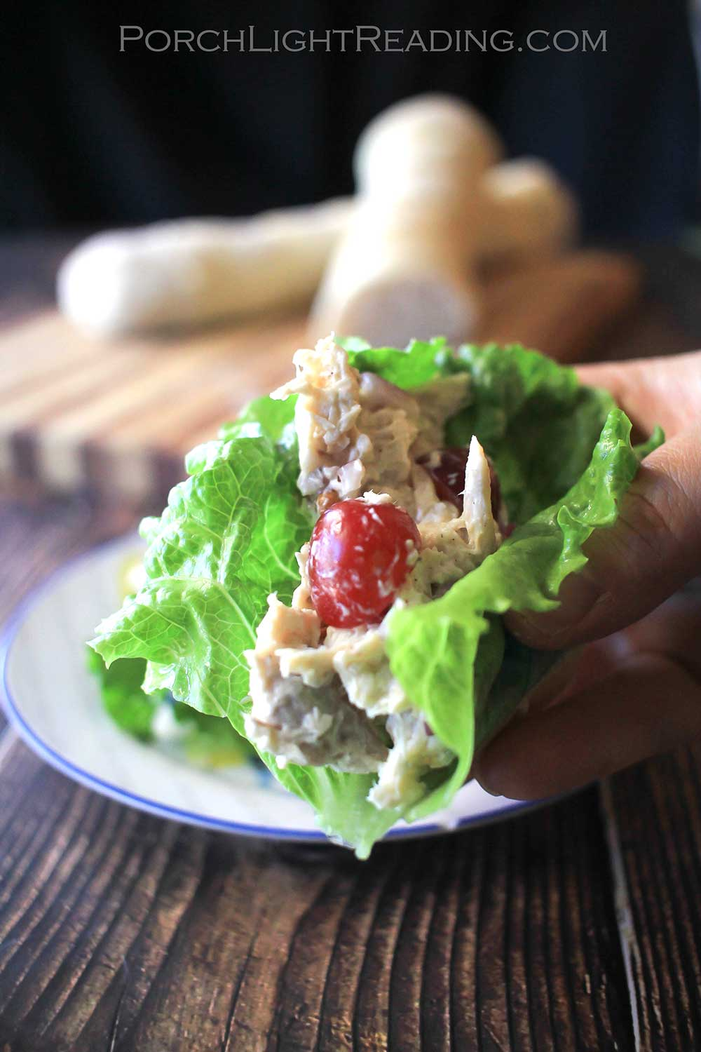 Chicken salad lettuce wrap with homemade French bread on a rustic cutting board.